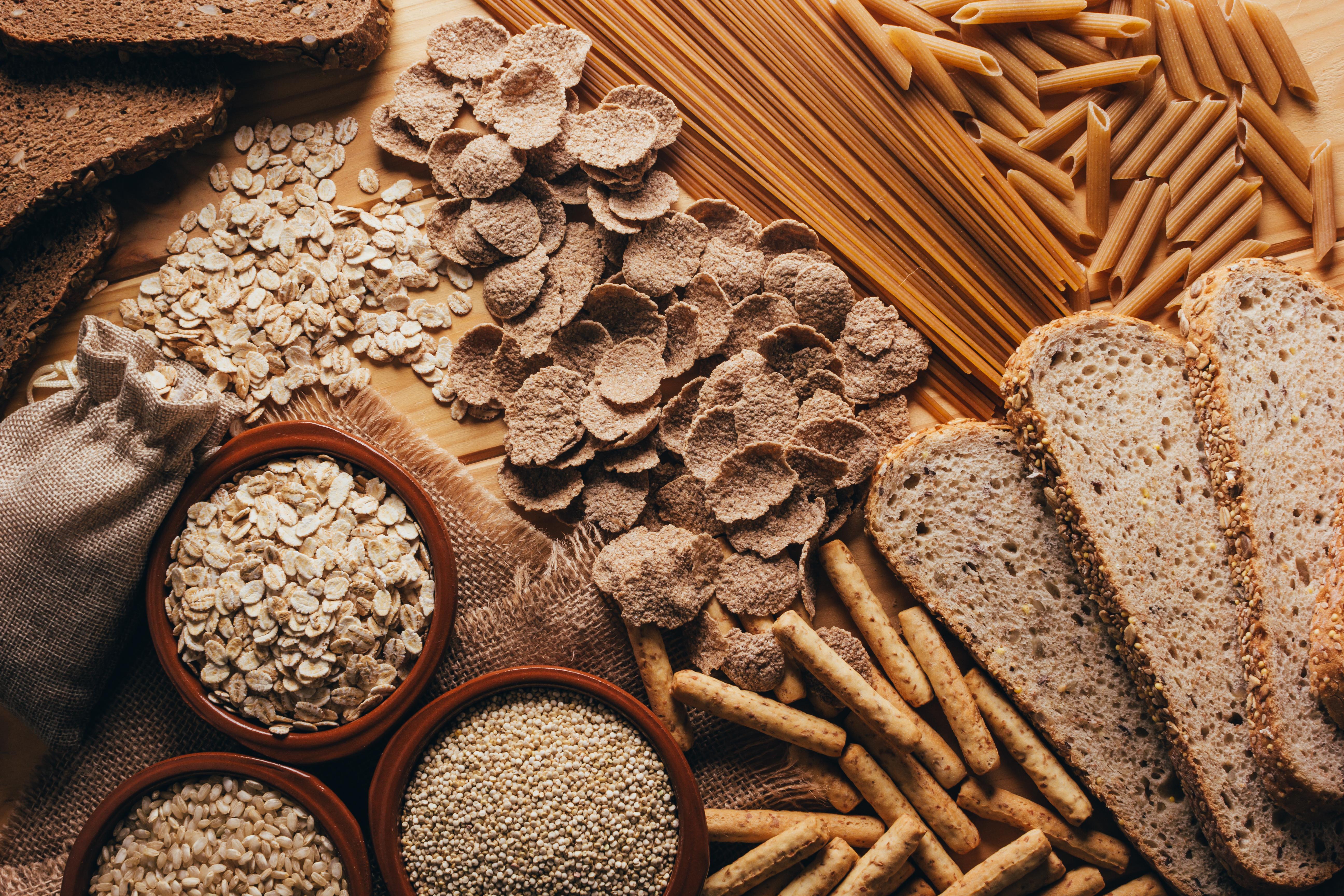 Einen Tisch mit verschiedenen Vollkornprodukten, wie zum Beispiel Nudeln, Brot und Haferflocken