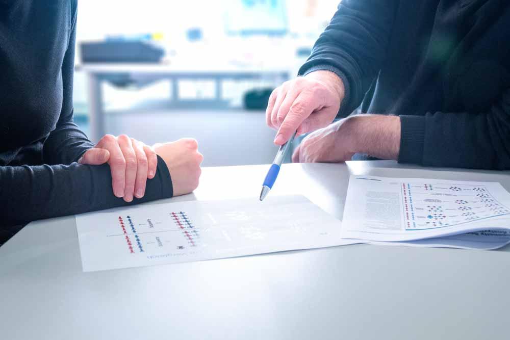 Zwei Personen besprechen auf dem Tisch liegende Papiere mit Diagrammen.