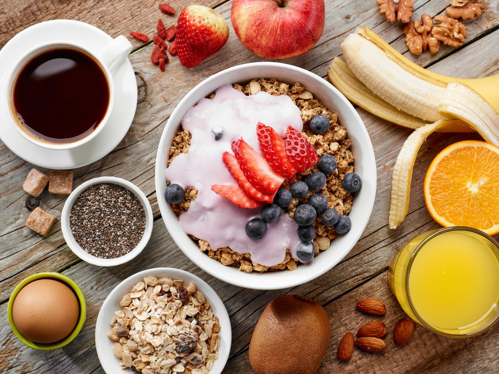 Auf einem Tisch ist ein Frühstück, bestehend aus Müsli, viel Obst und Nüssen sowie einem Ei und Kaffee angerichtet
