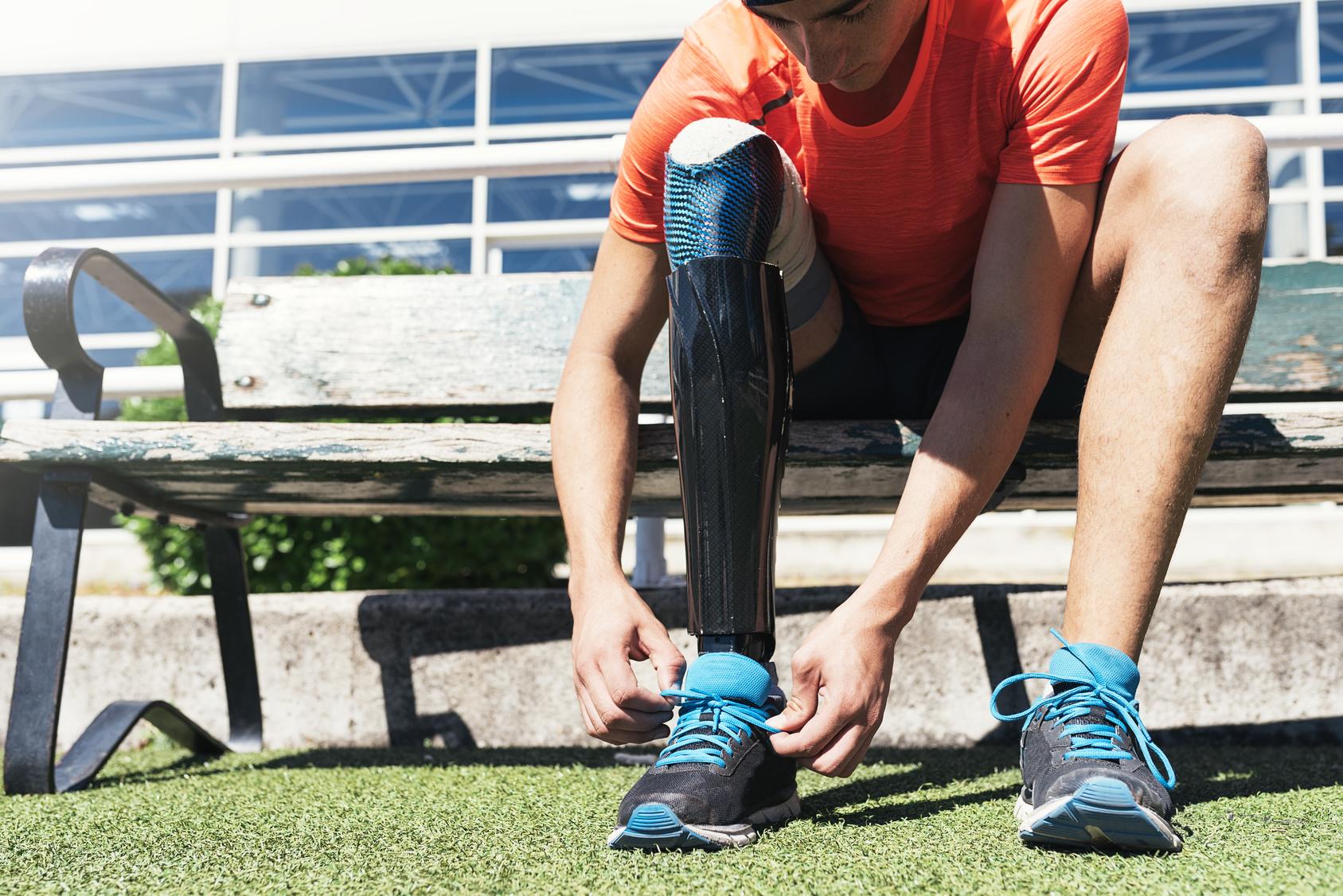 Ein junger Mann mit einer Beinprothese schnürt sich die Sportschuhe