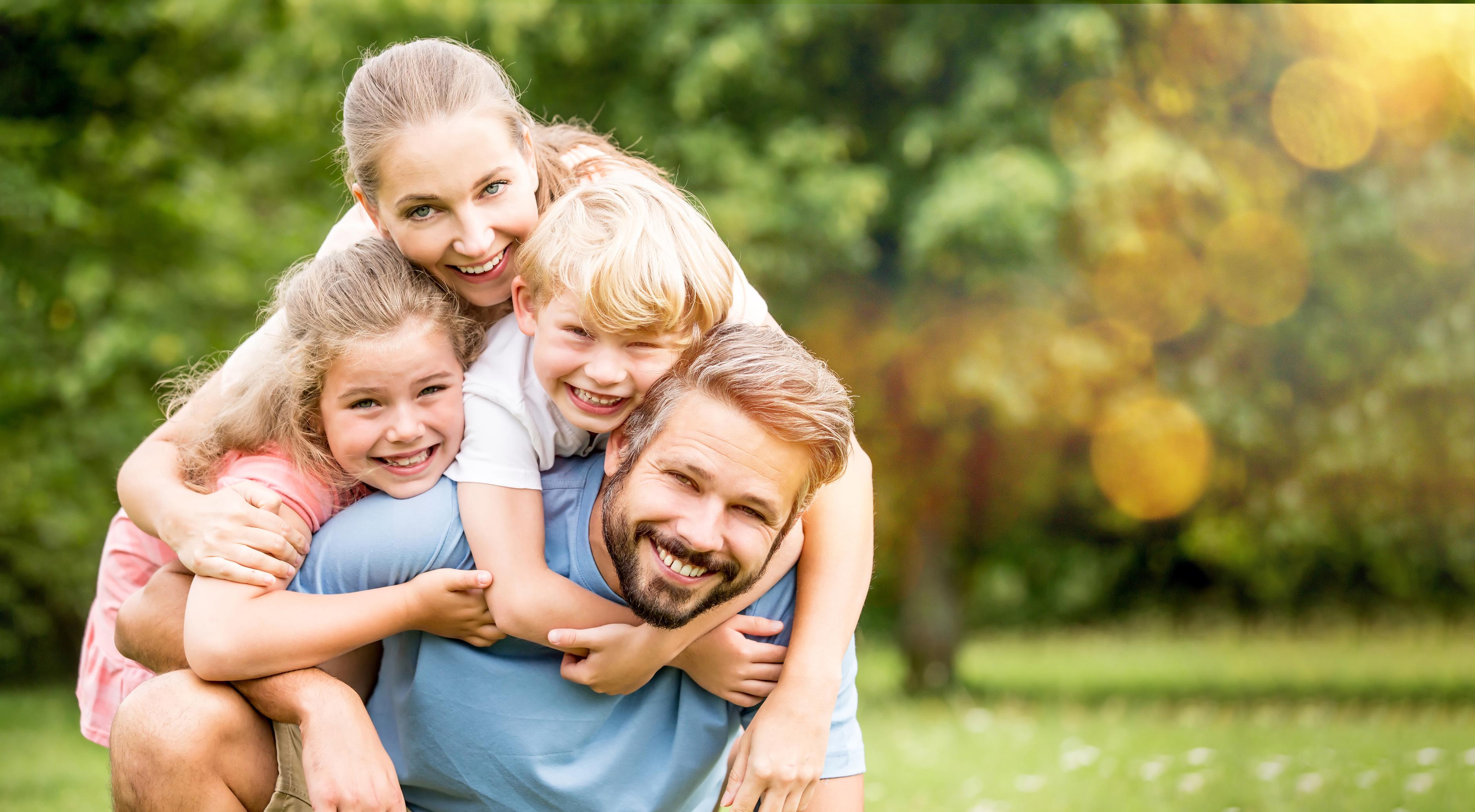 Eine Familie mit zwei Kindern lacht eng umschlungen in die Kamera
