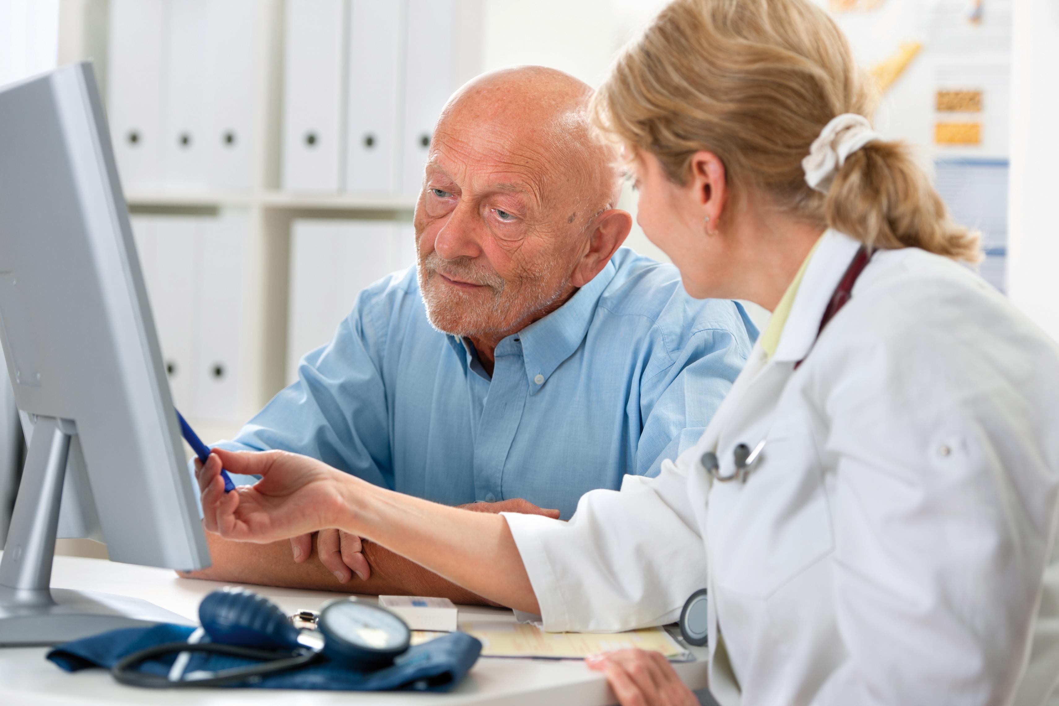 Eine Ärztin zeigt einem älteren Herren etwas auf dem Computer
