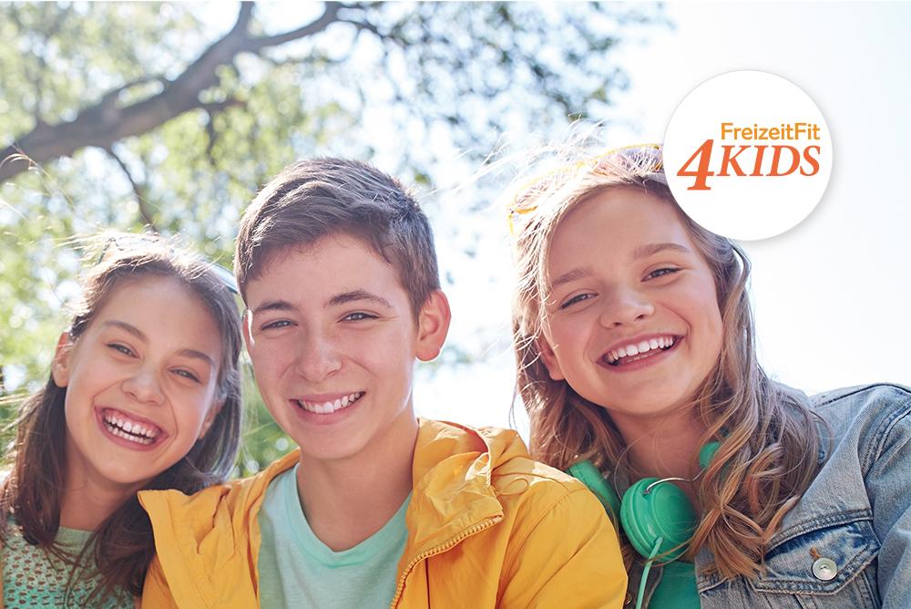 Drei Kinder lächeln in der Sonne. In der oberen rechten Ecke des Bildes ist das Logo von FreizeitFit4Kids, ein Projekt des Regionalen Innovations-Netzwerk (RIN) Diabetes, platziert