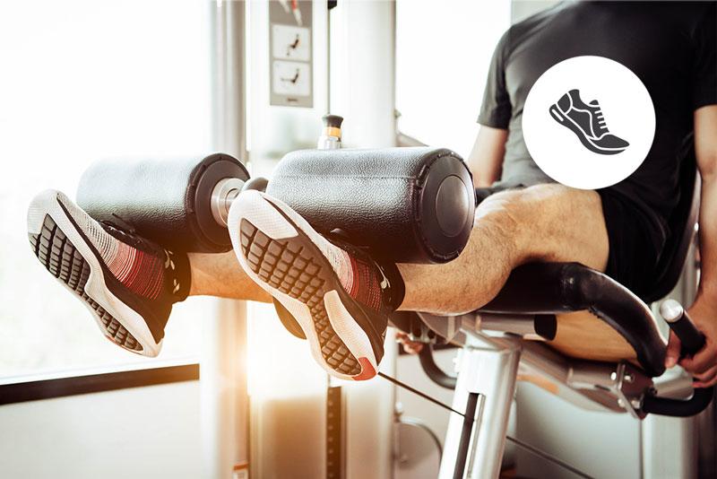 Ein Mann sitzt auf einem Fitnessgerät zur Stärkung der Beinmuskeln. Oben rechts befindet sich ein Icon mit einem Laufschuh